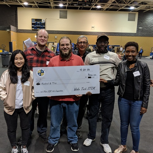 group of engineering students holding large check