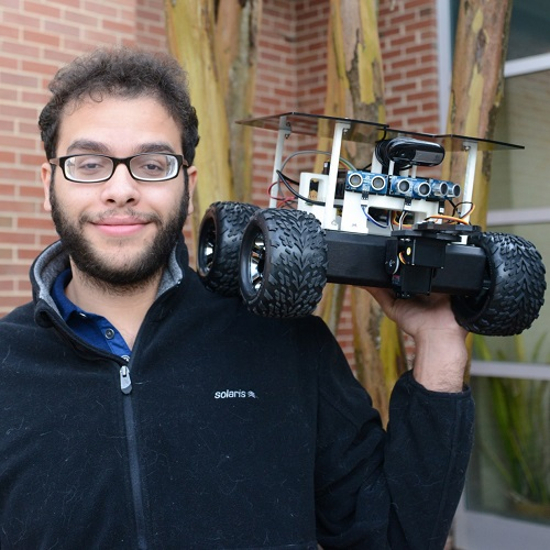 headshot of Mohamed standing in front of tree and holding up rover on his left shoulder
