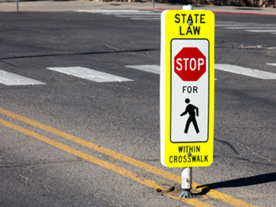 crosswalk with signage State Law Stop for pedestrian within crosswalk