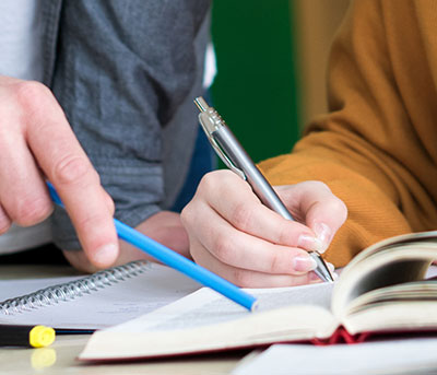 student writes in a book at tutor points to text with his pen