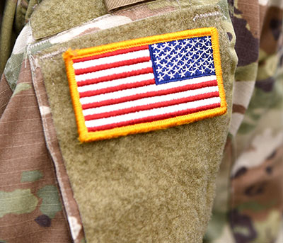 close up of US flag patch on a camouflage military uniform