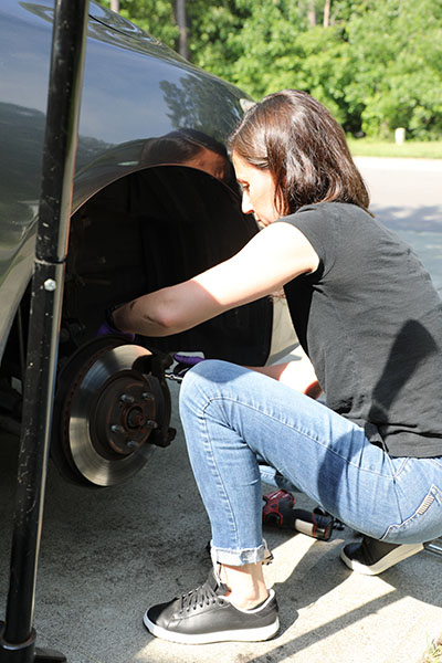 female automotive graduate fixes her car