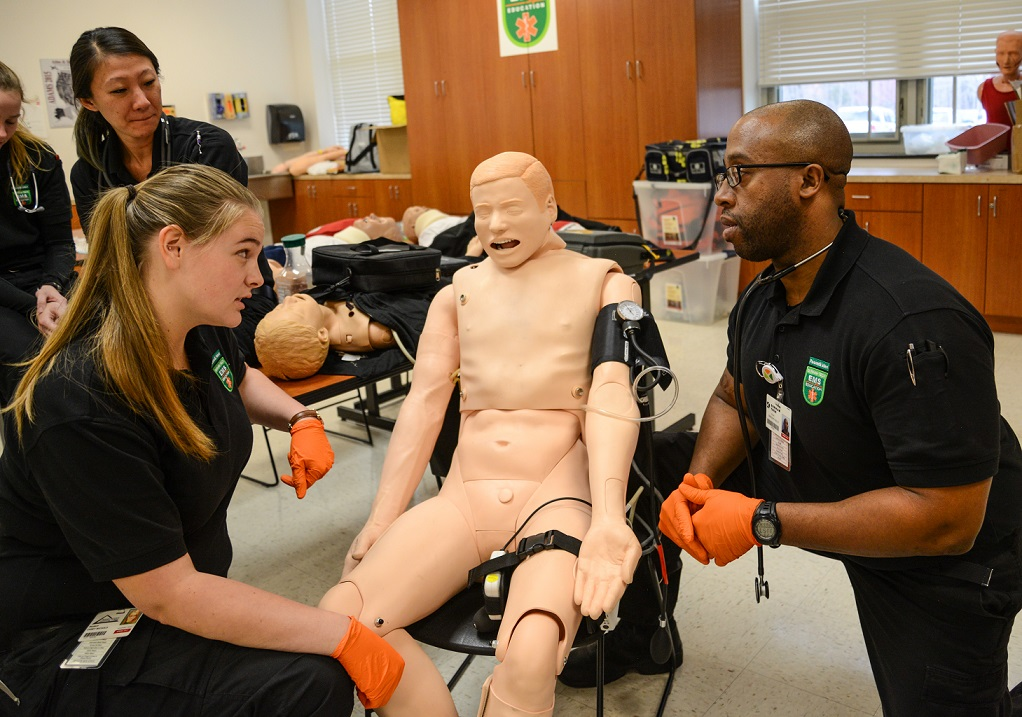 two students practice scenario on mannequin