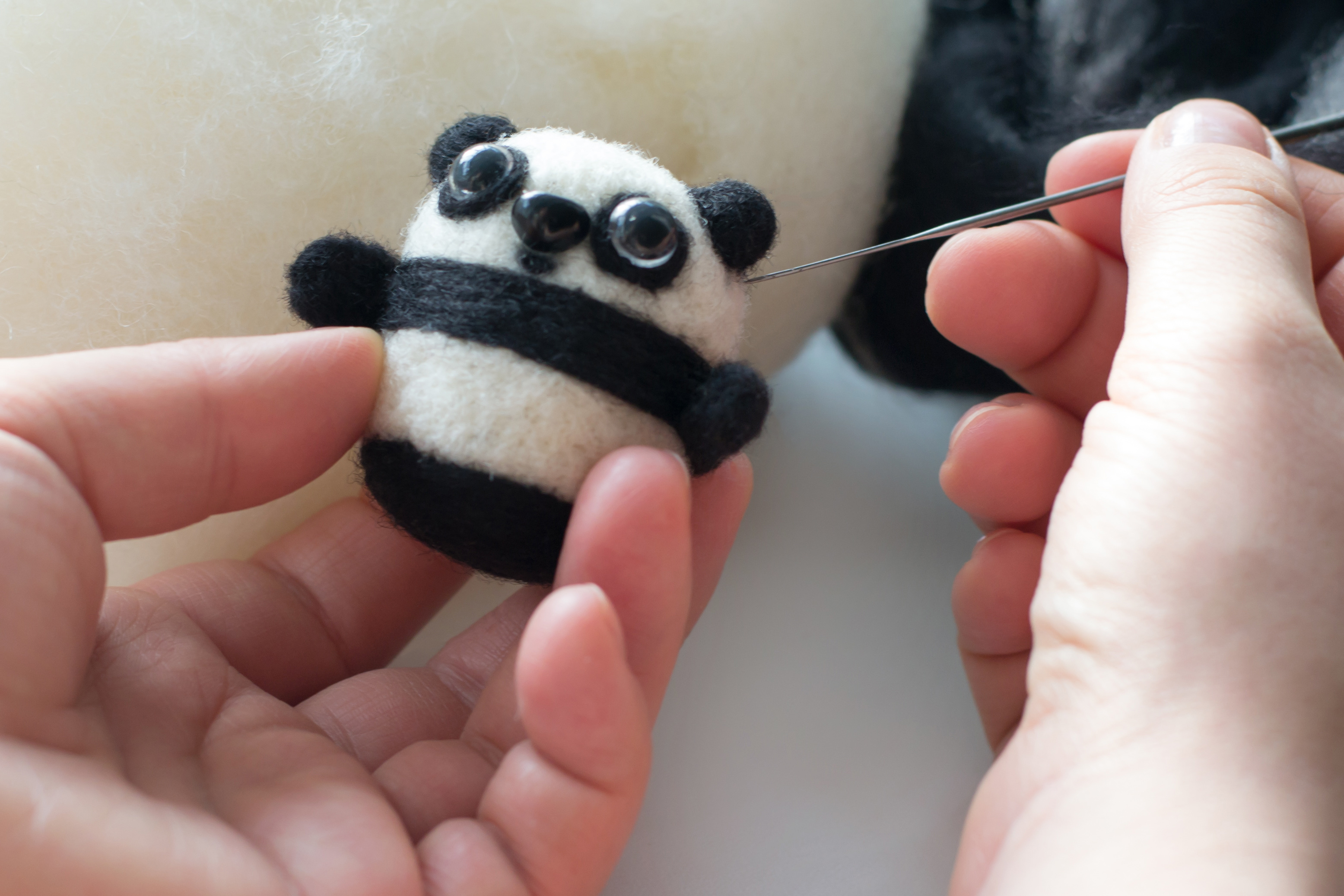 two hands holding wool felted panda