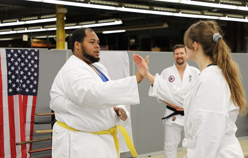 two students practice aikido ove, raising arms, crossed, while instructor looks on