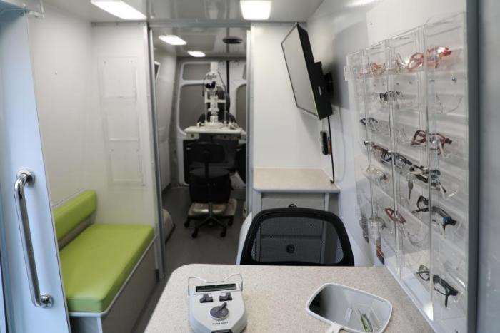 inside mobile health lab glasses on wall green seating and two chairs with tv screen on wall