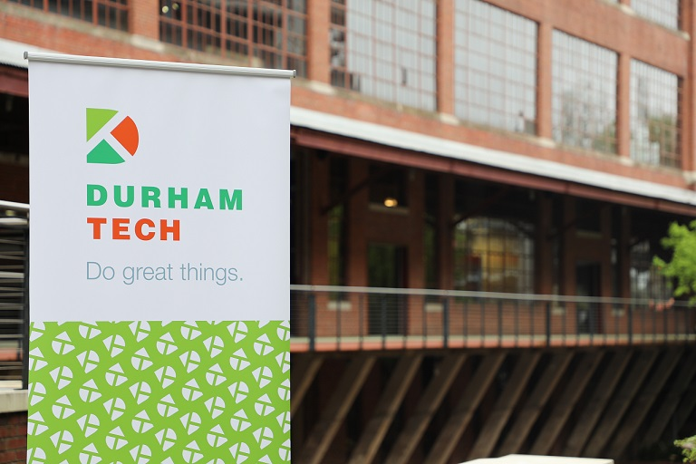 sign of durham tech logo in front of brick building