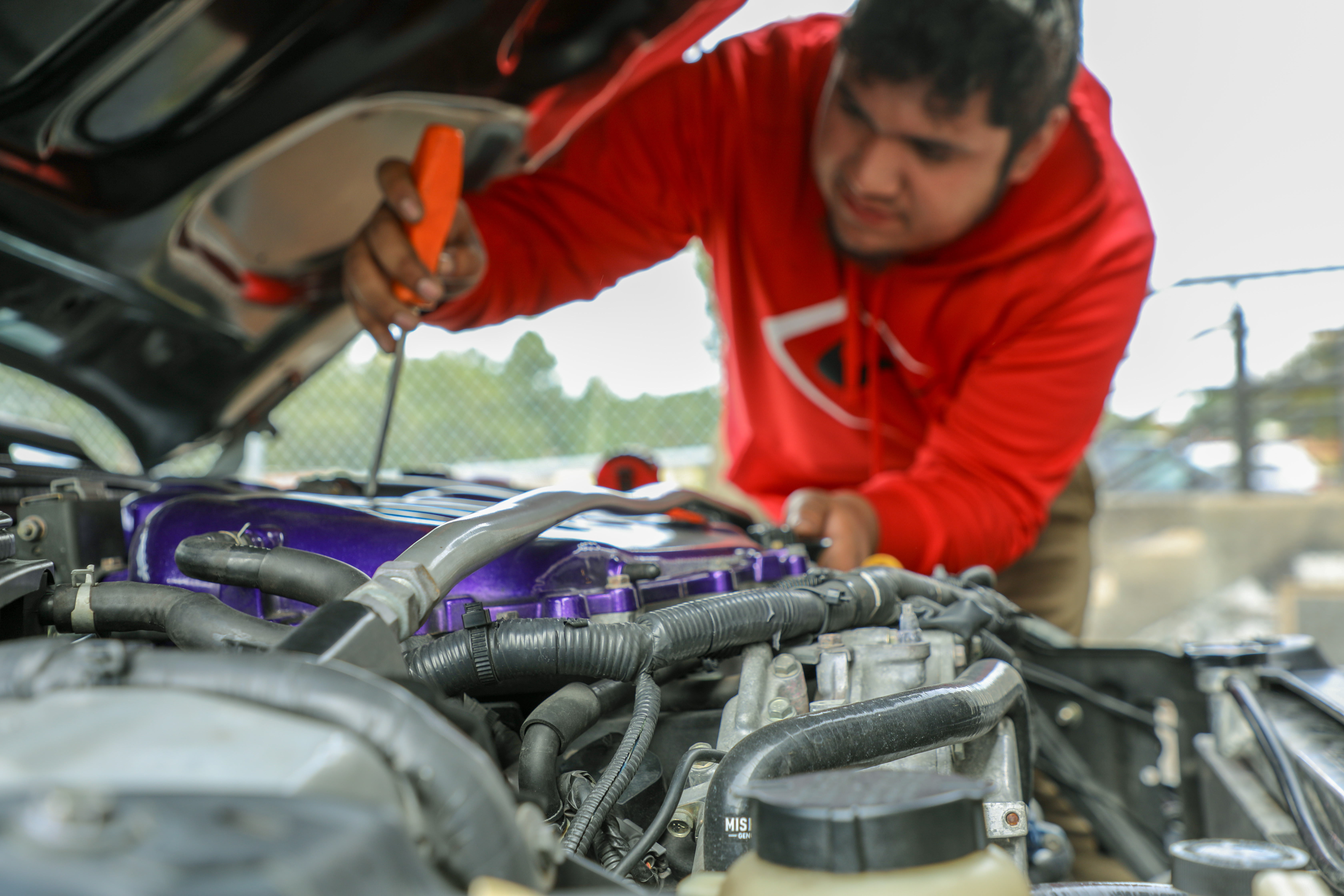 student in red hoodie leaning over car and looking at engine with screwdriver in hand