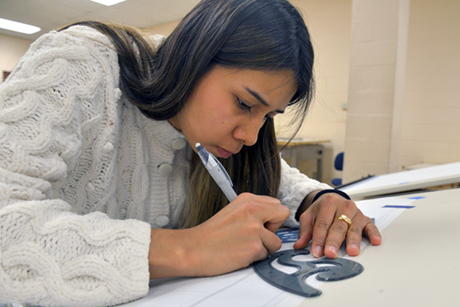 Female Architectural Technology student traces drafting outline in class.