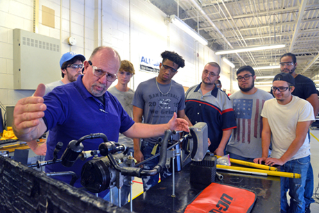 An instructor in the Automotive Systems Technology program uses right hand to indicate length for a for a group of eight Durham Tech students.