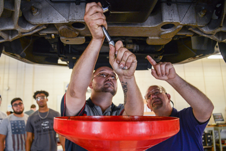A Durham Tech student uses two hands on a wrench to remove an oil cap while an automotive program instructor points to the bolt.