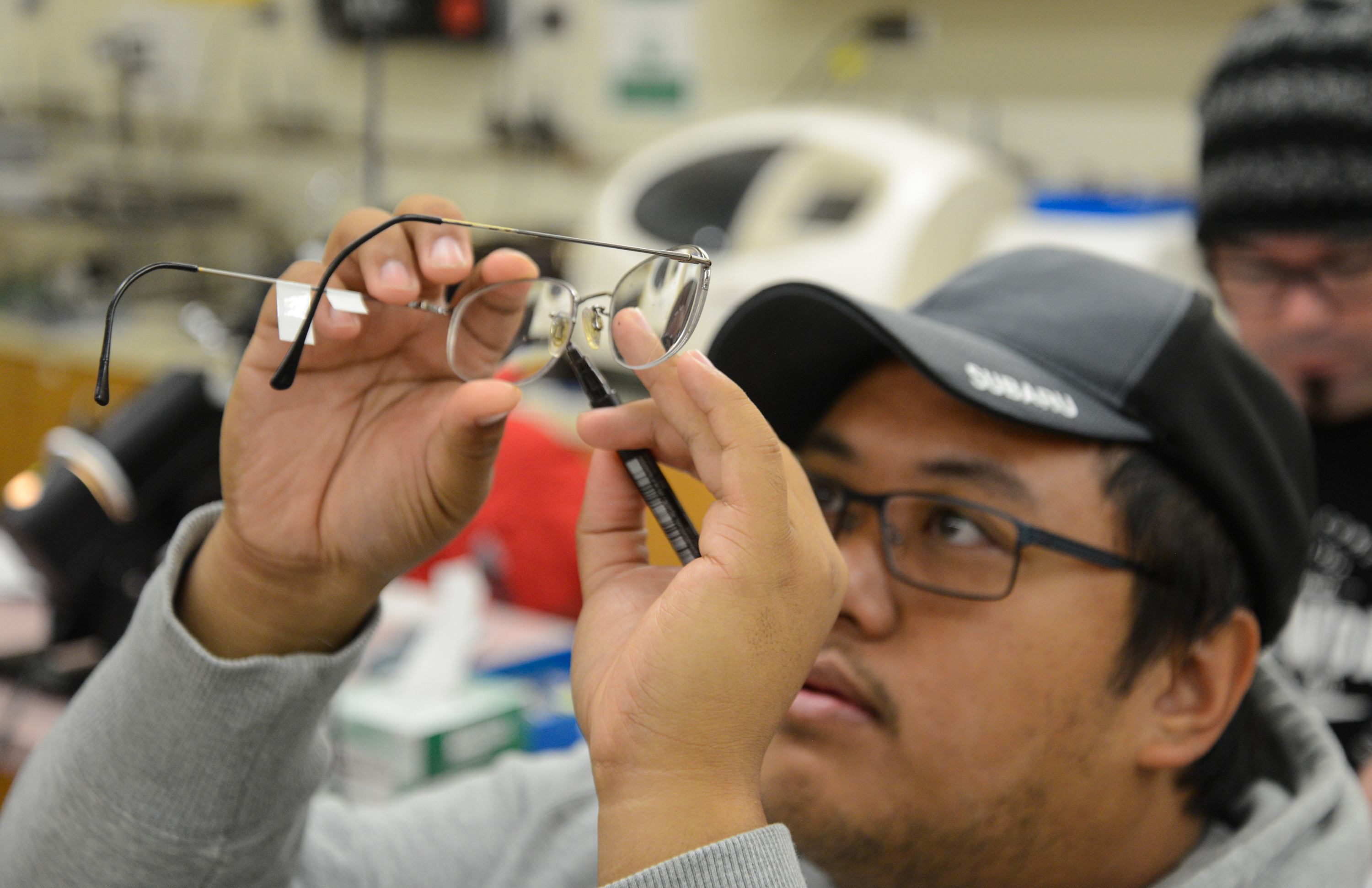 student holding up a pair of glasses and looking at them closely
