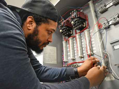 male student working with wires on electrical board