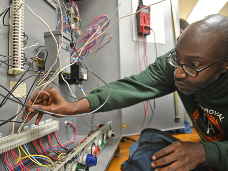 adult male student inserts wire into electrical board