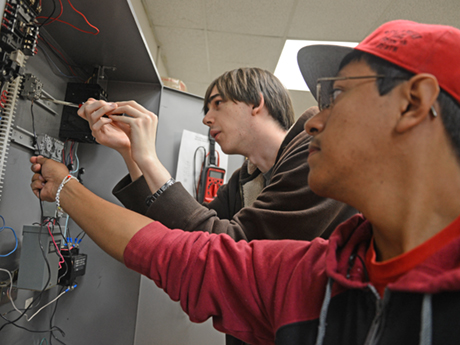 male students using tools on electrical system