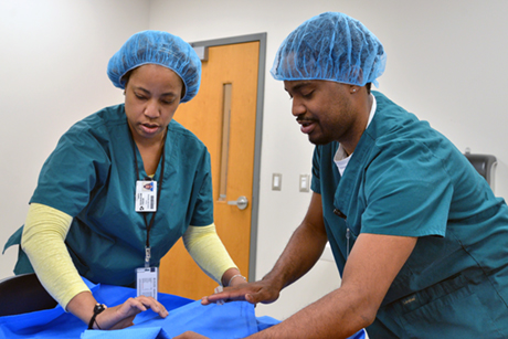 A male and female student wearing medical scrubs carefully lift a cloth sheet during a Central Sterile Processing class at Durham Tech.