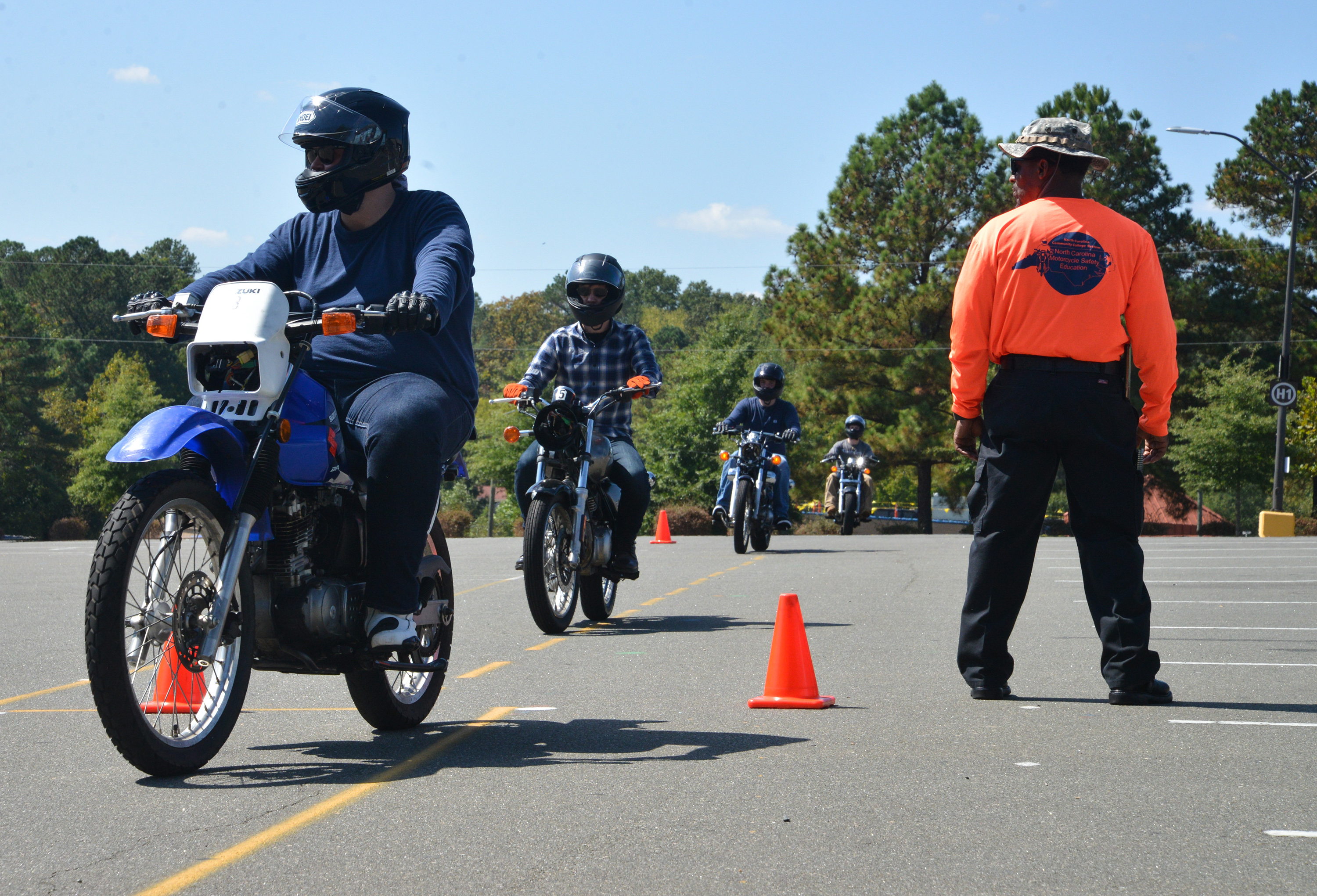 motorcyclists drive around orange cones while instructor supervises