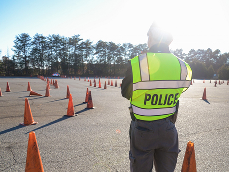 A Basic Law Enforcement Training instructor stands in uniform with a neon yellow police vest on while looking out over a road training course with orange cones.