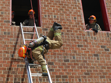A student firefighter climbs down a ladder while suspended upside down by a rope on the side of a brick training tower. Fellow students look out of two separate windows down at the suspended student.