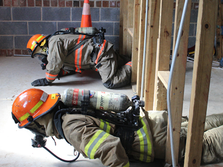 Two student firefighters crawl from right to left through a gap between wooden planks during a training exercise.