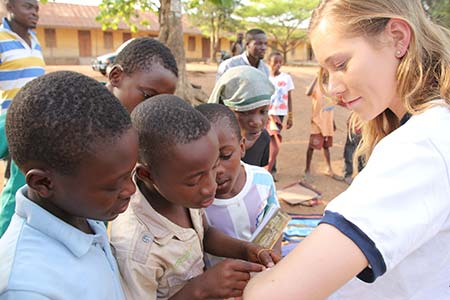 Ghana primary school students count freckles on study abroad student