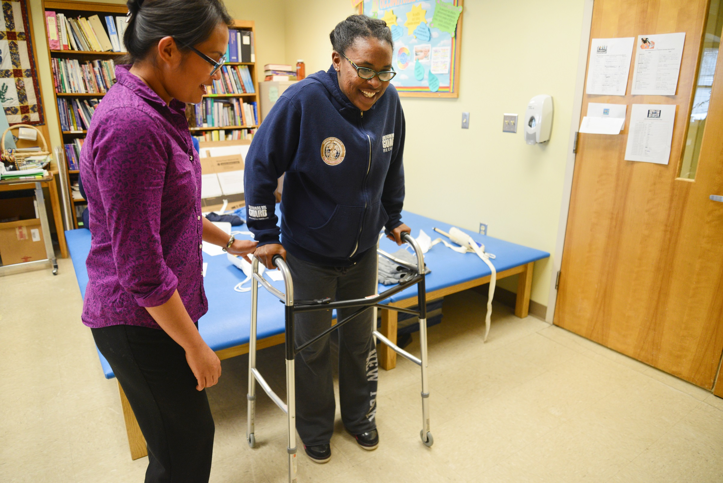 one student using a walker and the other helping