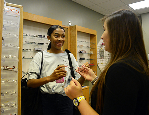 Opticianry student assists a college student in trying on glasses
