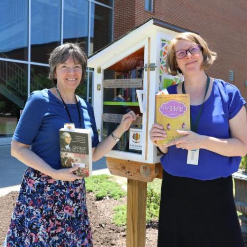 library staff with little free library on main campus